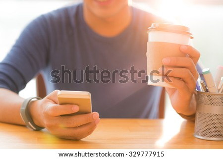 Young man having morning coffee and reading news in his smartphone - stock photo