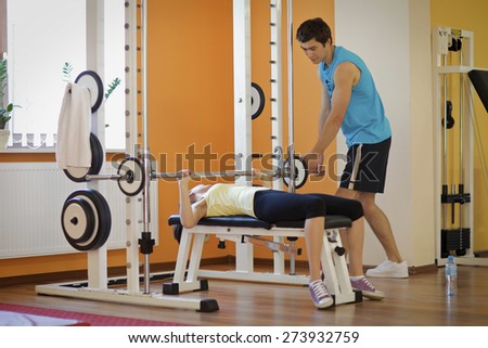 Young man helping a young woman lift a barbell on a bench - stock photo