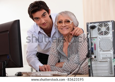 Young man helping an elderly lady use a computer - stock photo