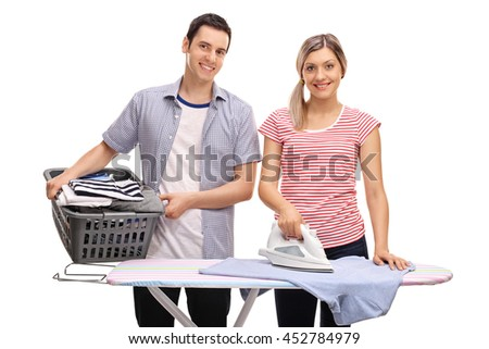 Young man helping his girlfriend with ironing clothes isolated on white background - stock photo