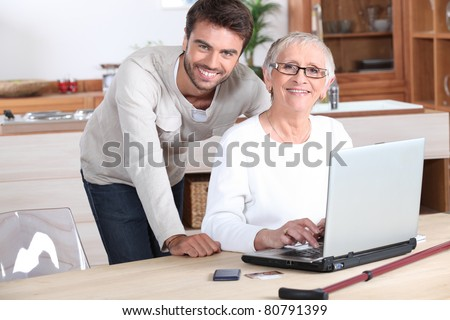 Young man helping senior woman with a laptop compute - stock photo