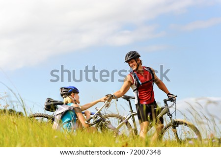 young man helps a fellow cyclist who has fallen over while mountain bicycle outdoors - stock photo
