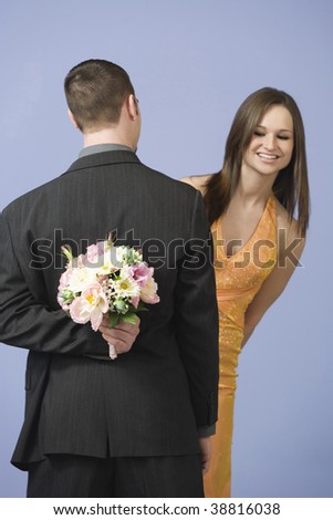 Young man hiding flowers behind his back from his partner. - stock photo