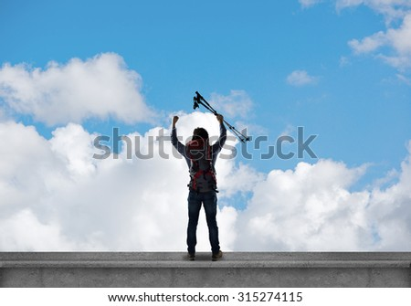 Young man hiker standing on top of city building