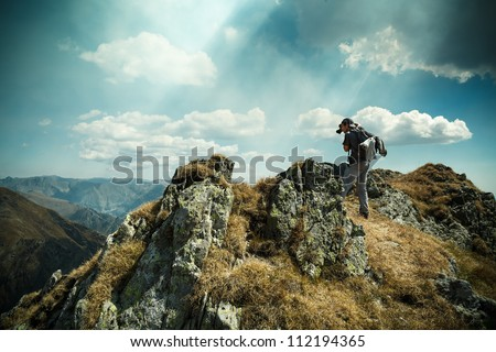 Young man hiking and taking photos from the top of the mountains - stock photo