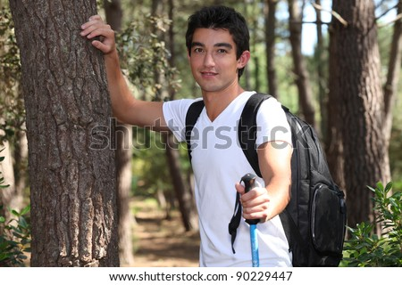 young man hiking in a pine forest - stock photo