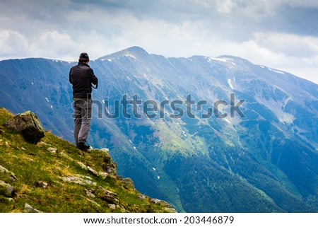 Young man hiking into the mountains in a spectacular landscape