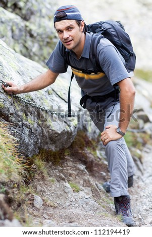 Young man hiking on difficult mountain trail - stock photo