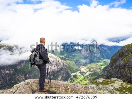 Young man hiking on kjerag. Happy man enjoy beautiful lake and good weather in Norway.