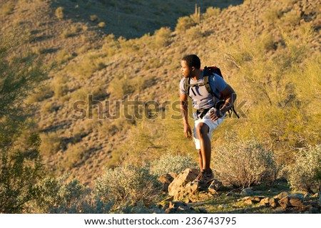 Young man hiking outdoors on a trail at Phoenix Sonoran Preserve in Phoenix, Arizona.