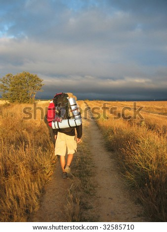 Young man hiking with backpack - stock photo
