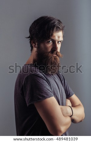 Young man hipster with fashion beard on serious sad face dark hair in shirt with crossing arms on breast posing on gray background studio