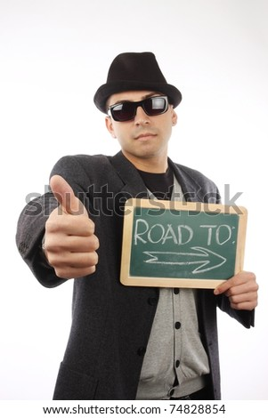 young man hitchhiking in studio - stock photo