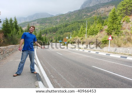 Young man hitchhiking on the road - stock photo
