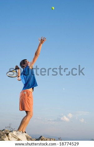 Young man hitting the tennis ball on top of the rocky
