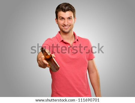 young man holding a beer isolated on grey background