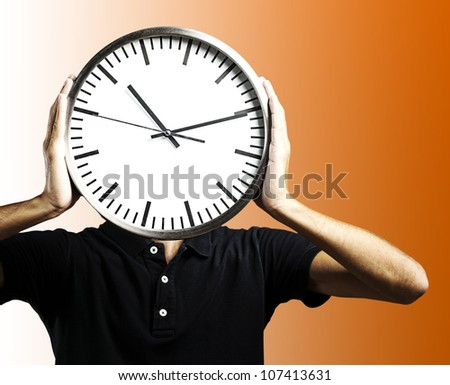 young man holding a big clock covering his face over an orange background - stock photo