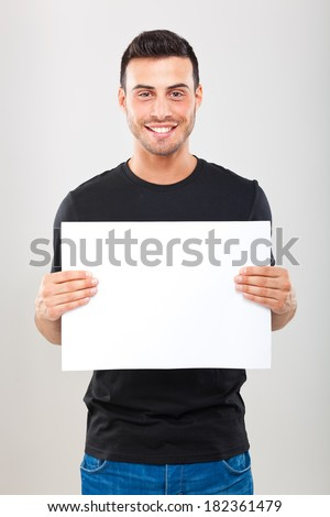 Young man holding a blank sheet - stock photo