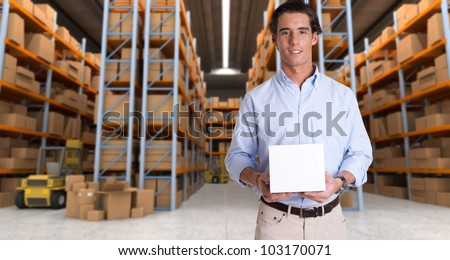Young man holding a blank white box in a distribution warehouse - stock photo