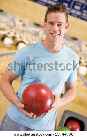 Young man holding a bowling ball in a bowling alley - stock photo