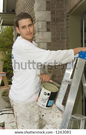 Young man, holding a can of paint and ladder - stock photo