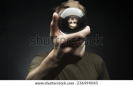 Young man holding a clear transparent crystal glass ball in their hand