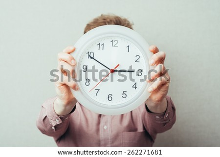young man holding a clock in hand - stock photo