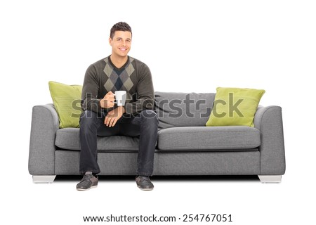 Young man holding a cup of coffee seated on sofa isolated on white background