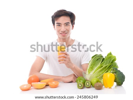 Young man holding a glass of orange juice and sitting next to a pile of fruits and vegetables isolated on white background - stock photo