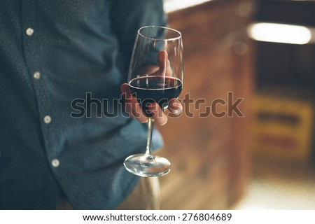 Young man holding a glass with red wine, bar on background - stock photo