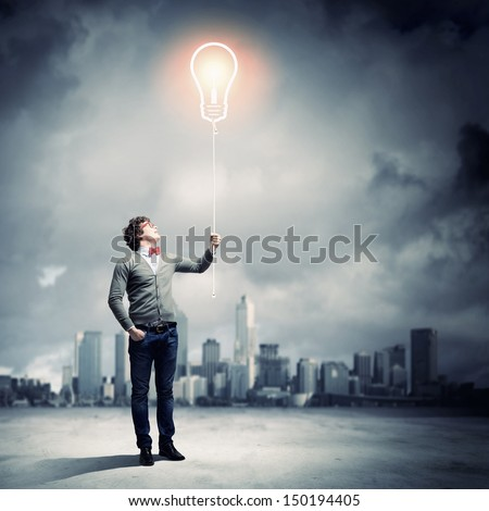 Young man holding a light at his hands against polluted and ruined landscape - stock photo