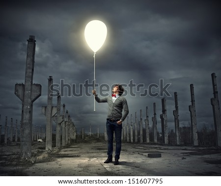 Young man holding a light at his hands against polluted and ruined landscape
