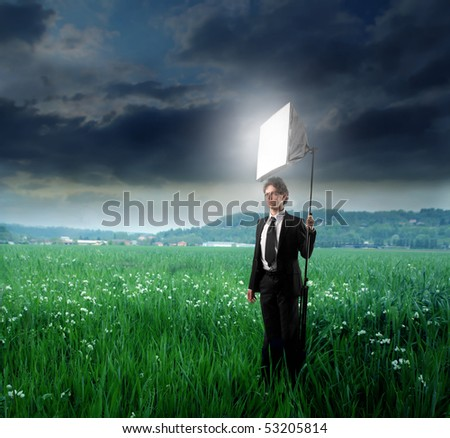 Young man holding a photographer lamp on a green meadow - stock photo