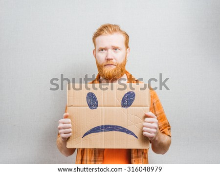 young man holding a picture of a sad - stock photo