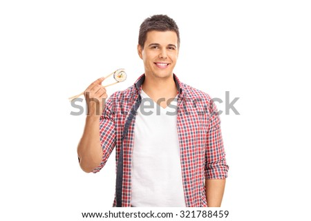 Young man holding a piece of sushi on Chinese sticks and looking at the camera isolated on white background - stock photo