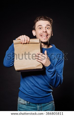 young man holding a plain wrapped package.  emotions, facial expressions, feelings, body language, signs. image on a black studio background. - stock photo