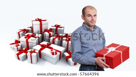 Young man holding a present against a background of gift boxes