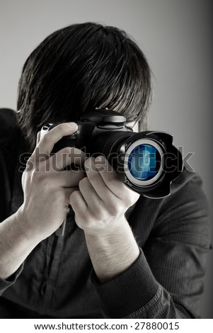Young man holding a professional DSLR camera and taking pictures - stock photo