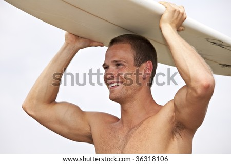 young man holding a surf board outdoors