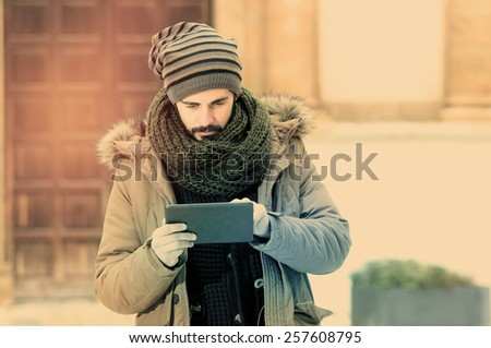 young man holding a tab�²et note pad with his right hand in an outdoor urban setting in instagram style - stock photo