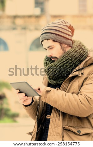young man holding a tabet n Mediterranean Country instagram filte applied - stock photo