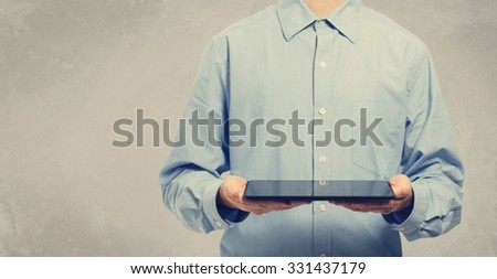 Young man holding a tablet computer on gray colored background - stock photo