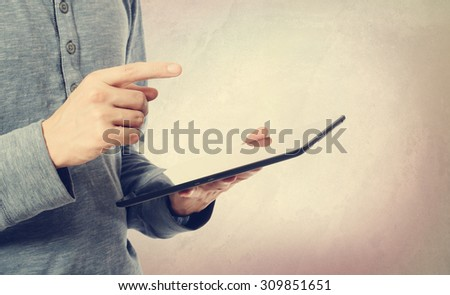 Young man holding a tablet computer on muted pastel background - stock photo