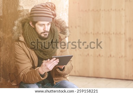 young man holding a tablet in  outdoor urban setting warm tone filter applied - stock photo