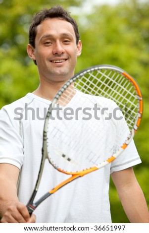 Young man holding a tennis racket outdoors - stock photo