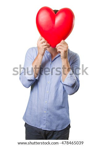 Young man holding a toy heart on white background