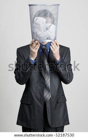 Young man holding a trash bin against his head, neutral background