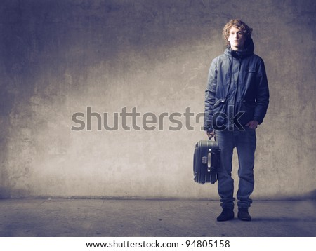 Young man holding a trolley case - stock photo
