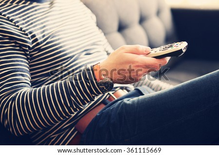 Young man holding a tv cable remote, watching tv. Life style, entertainment, young people. fashion, design  and interior concept - stock photo
