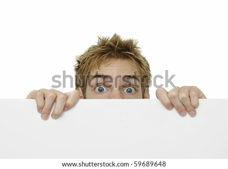 Young man holding a white cardboard sign peeking above it with copyspace above and below - stock photo